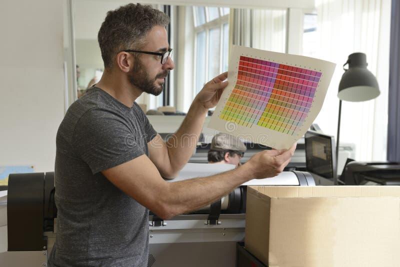 De grafische ontwerper controleert de kleur met kleurenmonster stock foto's