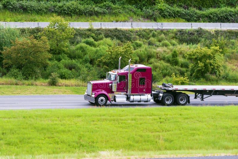 De grand capot rouge foncé d'installation d'Américain camion classique semi avec de couche horizontale la remorque vide semi cond photo libre de droits