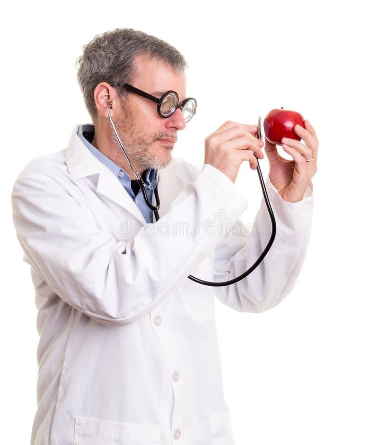 De grappige Arts onderzoekt een appel royalty-vrije stock foto