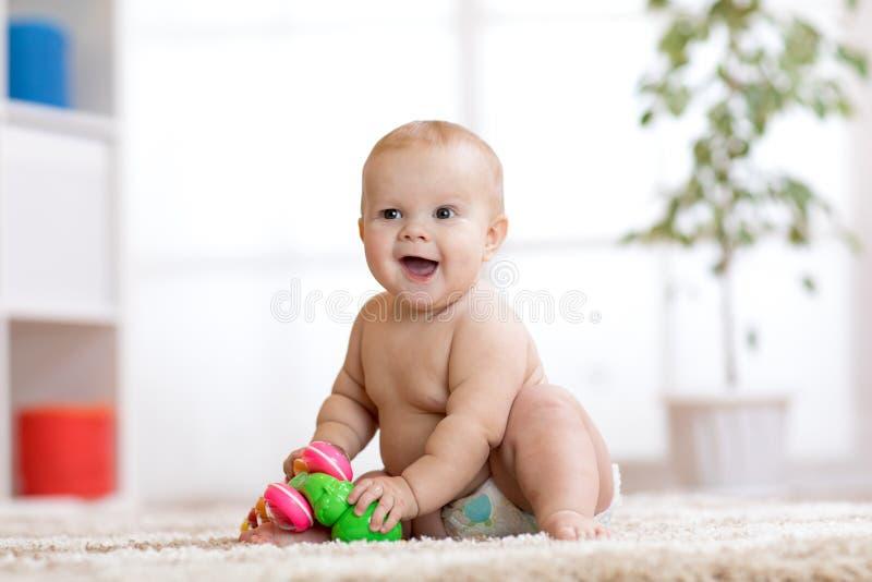 De grappige baby in luier zit op tapijt en speelt thuis met stuk speelgoed Ondiepe Diepte van Gebied royalty-vrije stock afbeelding
