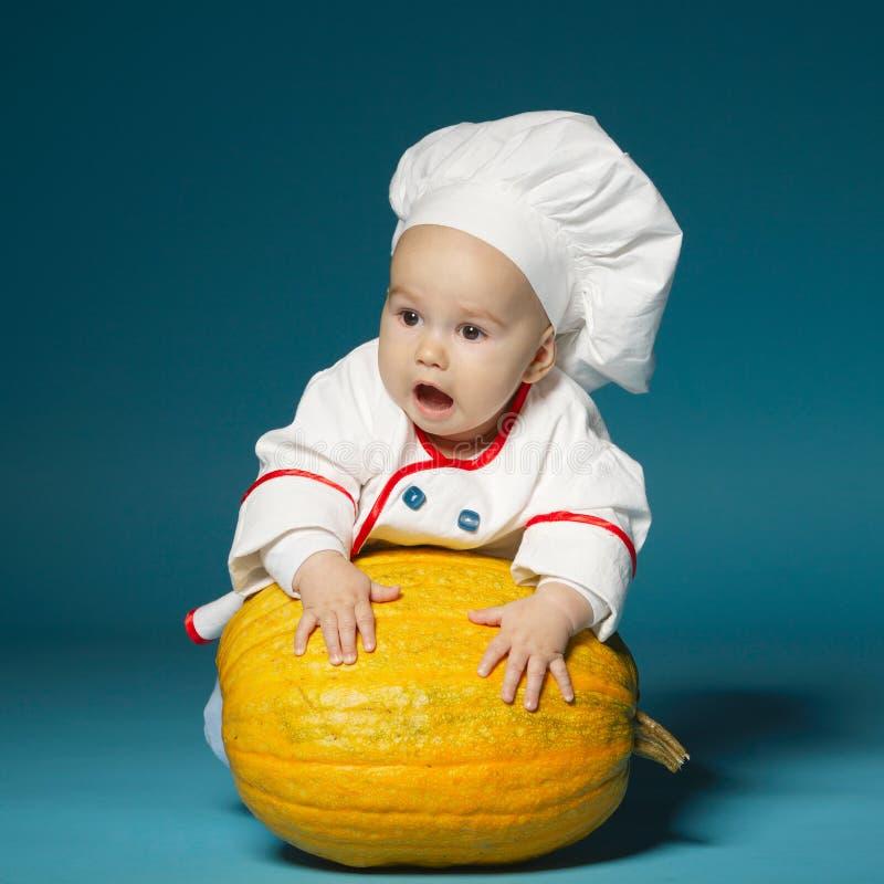 De grappige baby met kokkostuum houdt pompoen royalty-vrije stock afbeelding