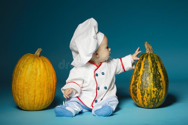 De grappige baby met kokkostuum houdt pompoen royalty-vrije stock foto