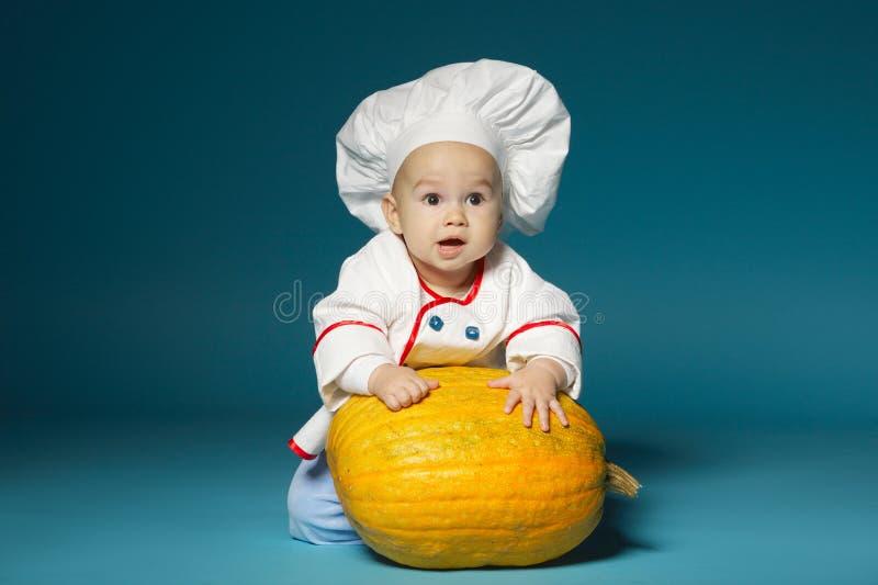 De grappige baby met kokkostuum houdt pompoen royalty-vrije stock foto's