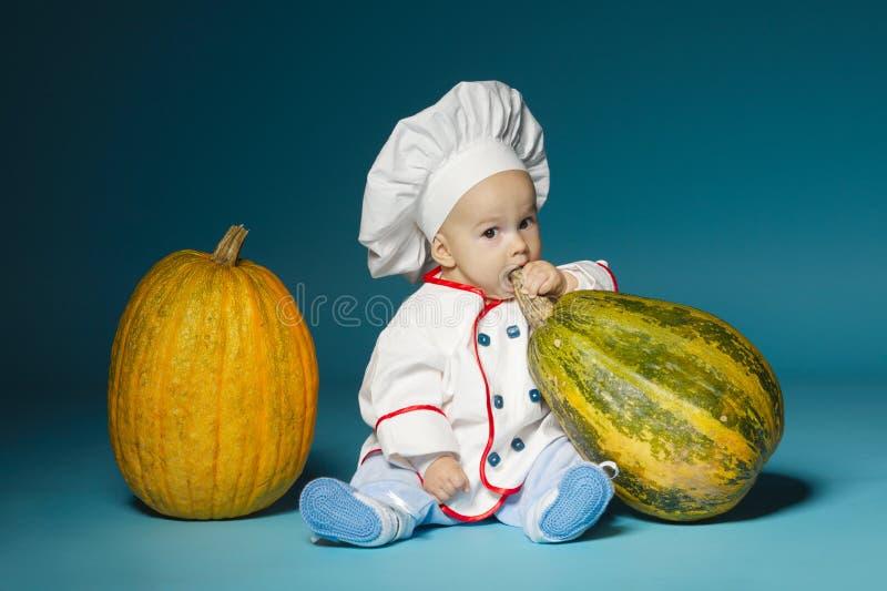 De grappige baby met kokkostuum houdt pompoen stock foto