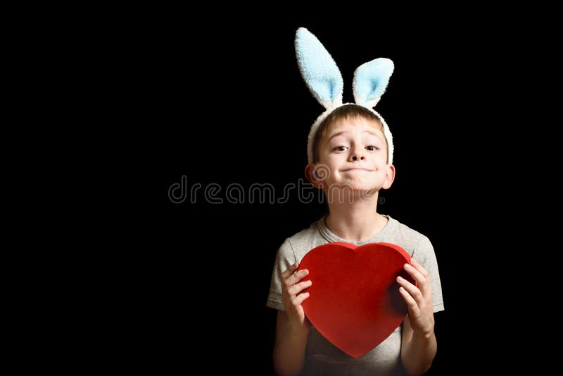 De grappige blonde jongen in hazenoren houdt de rode doos van de hartvorm op zwarte achtergrond Liefde en Familieconcept Exemplaa stock afbeeldingen