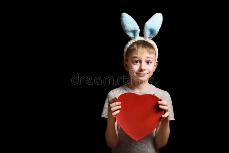 De grappige blonde jongen in hazenoren houdt de rode doos van de hartvorm op zwarte achtergrond Liefde en Familieconcept Exemplaa stock fotografie