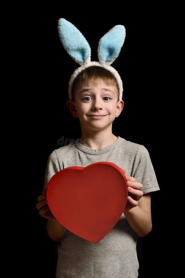 De grappige blonde jongen in hazenoren houdt de rode doos van de hartvorm op zwarte achtergrond Liefde en Familieconcept Verticaa royalty-vrije stock afbeelding