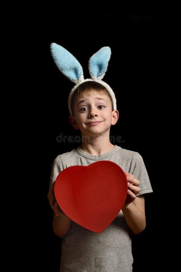 De grappige blonde jongen in hazenoren houdt de rode doos van de hartvorm op zwarte achtergrond Liefde en Familieconcept Verticaa royalty-vrije stock afbeeldingen