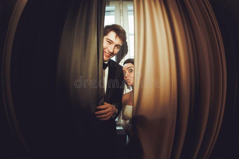 De grappige bruidtribunes achter het glimlachen verzorgen verborgen onder curta stock fotografie