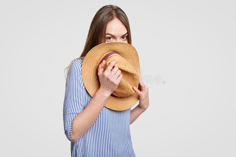 De grappige dame met donker recht haar, huiden achter strohoed, heeft pret, gekleed in modieuze blouse, over witte achtergrond PB stock afbeelding