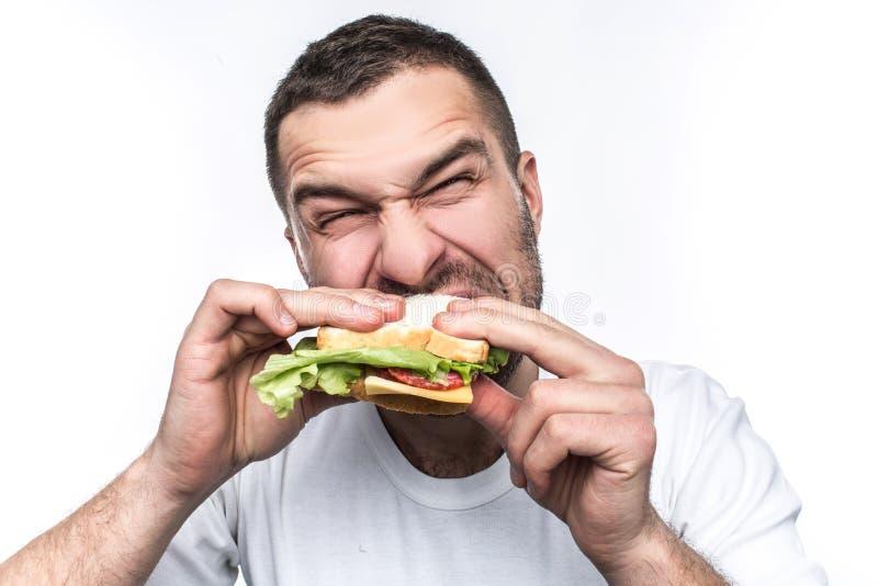 De grappige en hongerige kerel eet wat snel voedsel Hij is hongerig als een wolf De mens bijt zeer harde sandwich geïsoleerde royalty-vrije stock fotografie