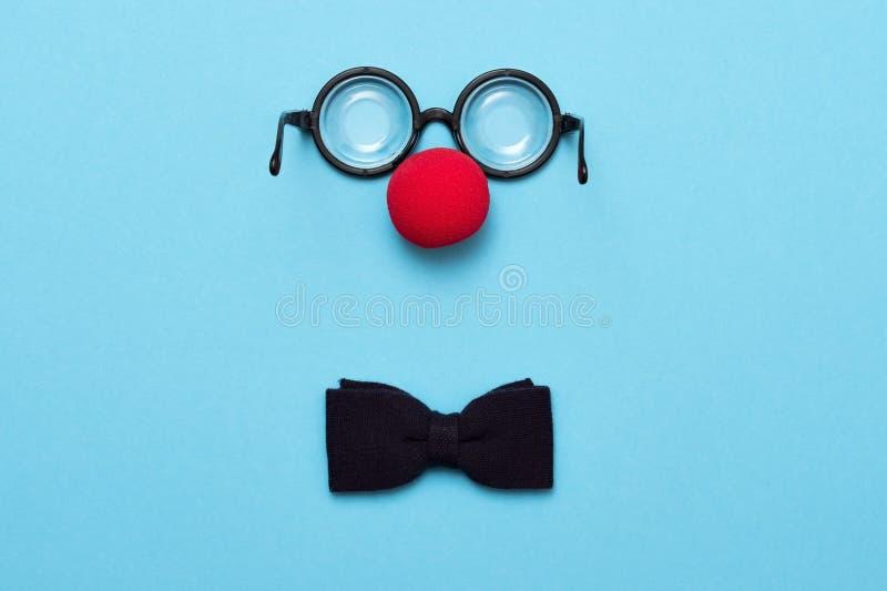 De grappige glazen, de rode clownneus en de band liggen op een gekleurde achtergrond, zoals een gezicht royalty-vrije stock foto's