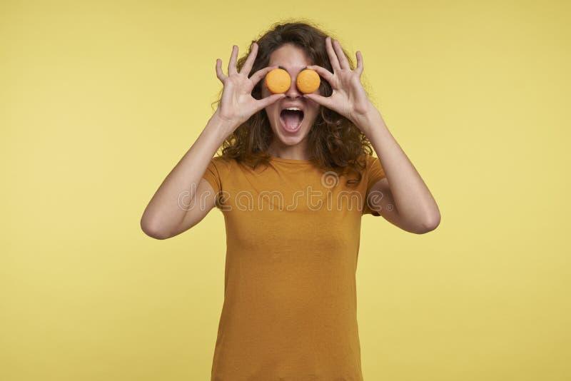De grappige glimlachende jonge donkerbruine die vrouw toont makarons voor de ogen, over gele achtergrond worden geïsoleerd stock afbeelding