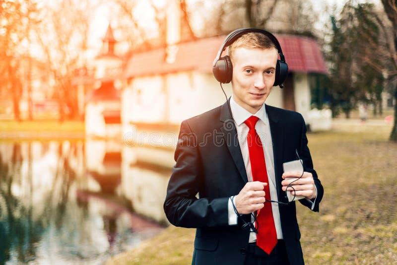 De grappige jonge kerel luistert aan muziek met grote hoofdtelefoons een mens in een zwart kostuum en een rode band zakenman die, stock fotografie