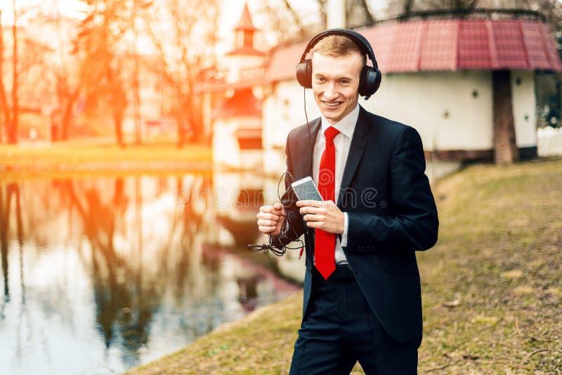 De grappige jonge kerel luistert aan muziek met grote hoofdtelefoons een mens in een zwart kostuum en een rode band zakenman die, royalty-vrije stock afbeelding