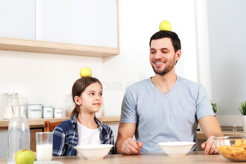 De grappige jonge papa en de dochter zitten naast elkaar, eten heerlijke cornflakes, houden appelen op hoofd, aantonen dat stock afbeelding
