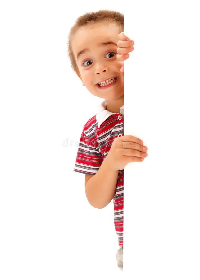 De grappige jongen bootst enge uitdrukking achter muur na stock afbeelding