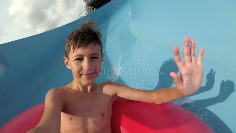 De grappige jongen daalt op de waterdia in het waterpark onderzoekt de camera royalty-vrije stock foto