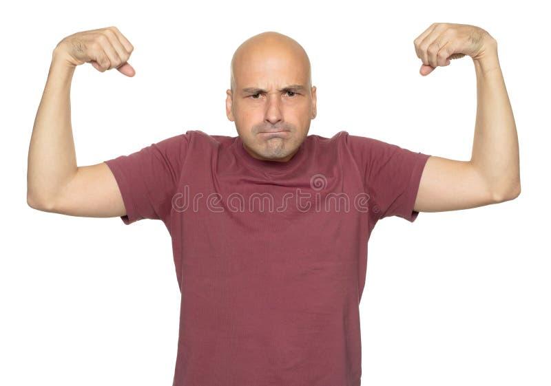 De grappige kale mens toont zijn spier stock fotografie