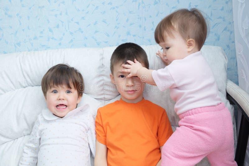De grappige kinderen knoeien rond, speelse gelukkige het lachen jonge geitjes, drie kinderen verschillende leeftijden die op bus  stock fotografie