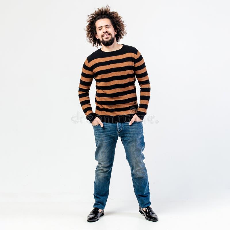 De grappige krullende kerel met een baard gekleed in een gestreepte zwarte en gele sweater en jeans stelt in de studio op het wit stock afbeelding