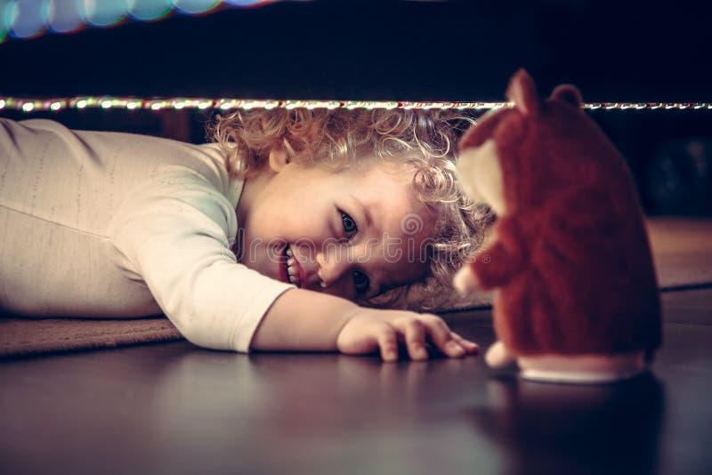 De grappige leuke het glimlachen baby het spelen huid - en - zoekt onder het bed met stuk speelgoed hamster in uitstekende stijl royalty-vrije stock foto