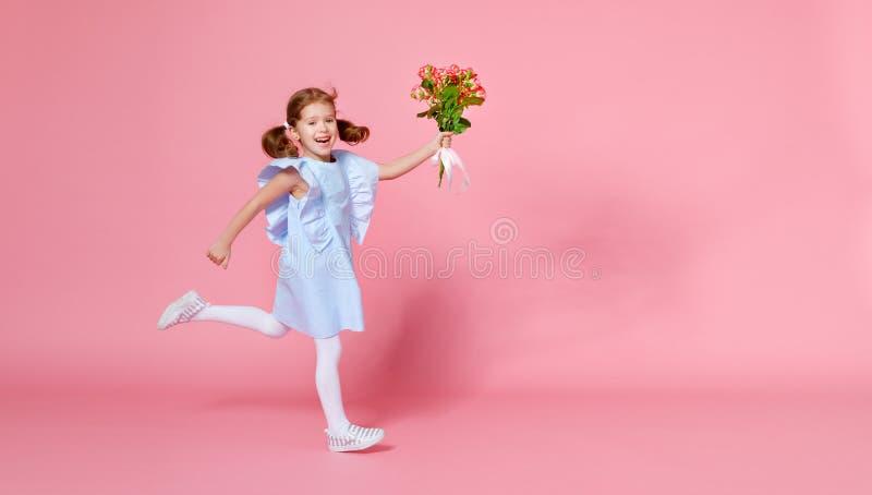 De de grappige looppas en sprongen van het kindmeisje met boeket van bloemen op kleur royalty-vrije stock afbeelding