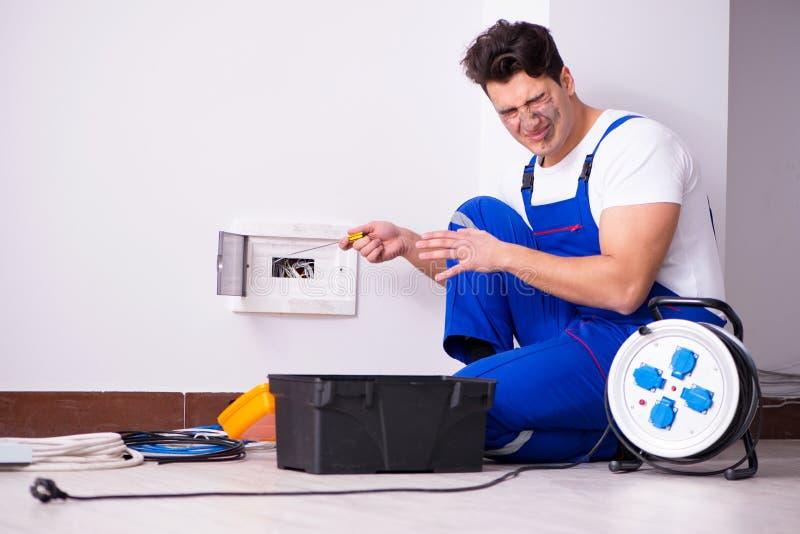 De grappige man die elektroreparaties thuis doen stock foto's
