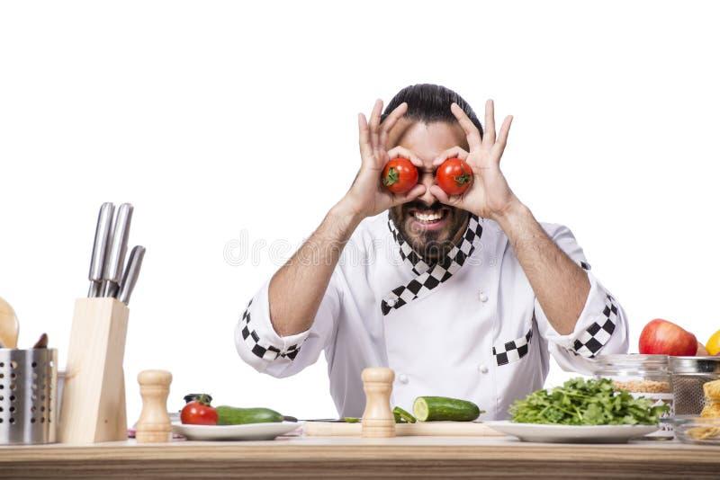 De grappige mannelijke kok die op de witte achtergrond wordt geïsoleerd stock foto