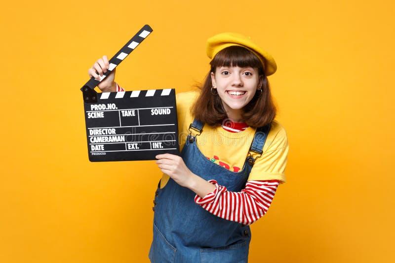 De grappige meisjestiener die in Franse baret, de klassieke zwarte film van de denim sundress holding clapperboard isoleerde op g royalty-vrije stock afbeeldingen