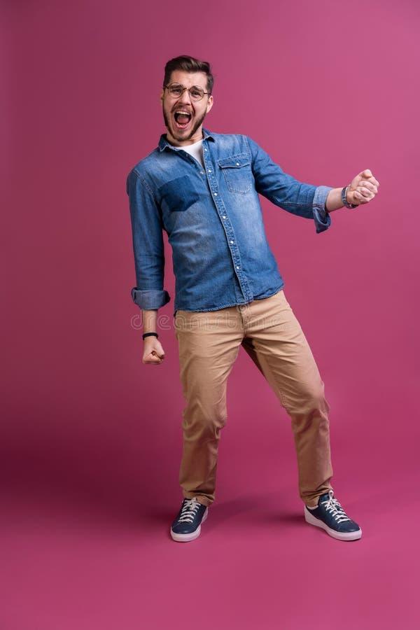 De grappige mens in toevallig heeft wat pret Hij stelt en danst Geïsoleerd op roze achtergrond royalty-vrije stock afbeeldingen