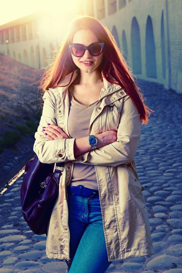 De grappige modieuze glimlachende mooie jonge redhairvrouw in hipster kleedt status in de straat met modieuze handtas royalty-vrije stock foto