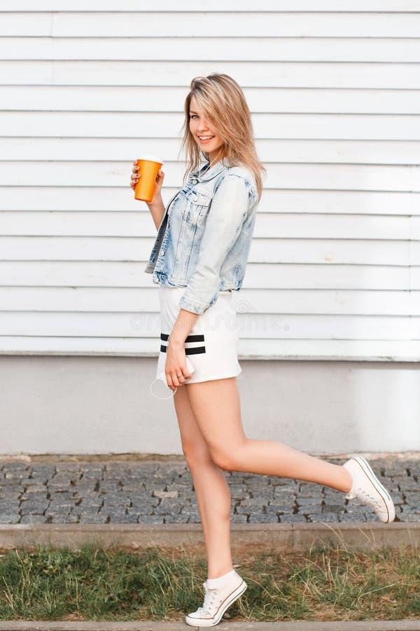 De grappige modieuze jonge vrouw in in sporten kleedt zich in blauw denimjasje in witte tennisschoenen met een oranje kop met een royalty-vrije stock afbeeldingen