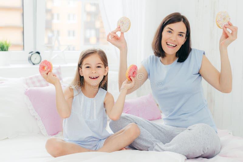 De grappige moeder en de dochter gekleed in nachthemden, hebben goede stemming in ochtend, greep smakelijke doughnuts, die desser royalty-vrije stock fotografie