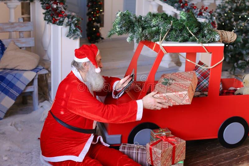 De grappige Santa Claus-wensen van lezingskinderen bij tablet en de inschrijving stock foto