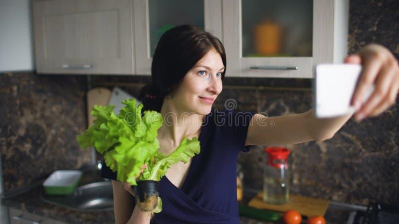 De grappige spruit van de vrouwenhuisvrouw selfie met groene salade terwijl thuis binnen het koken in de keuken stock afbeelding