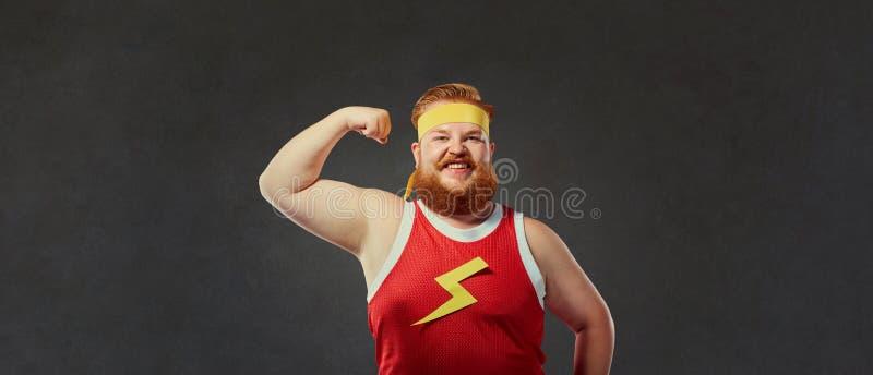De grappige vette mens in sportenkleren toont een hand met spierenbicepsen stock afbeeldingen