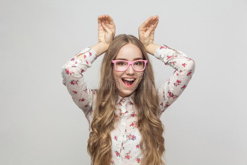 De grappige vrouw die in roze glazen handen houden kijkt ` s zoals konijnoor royalty-vrije stock afbeelding