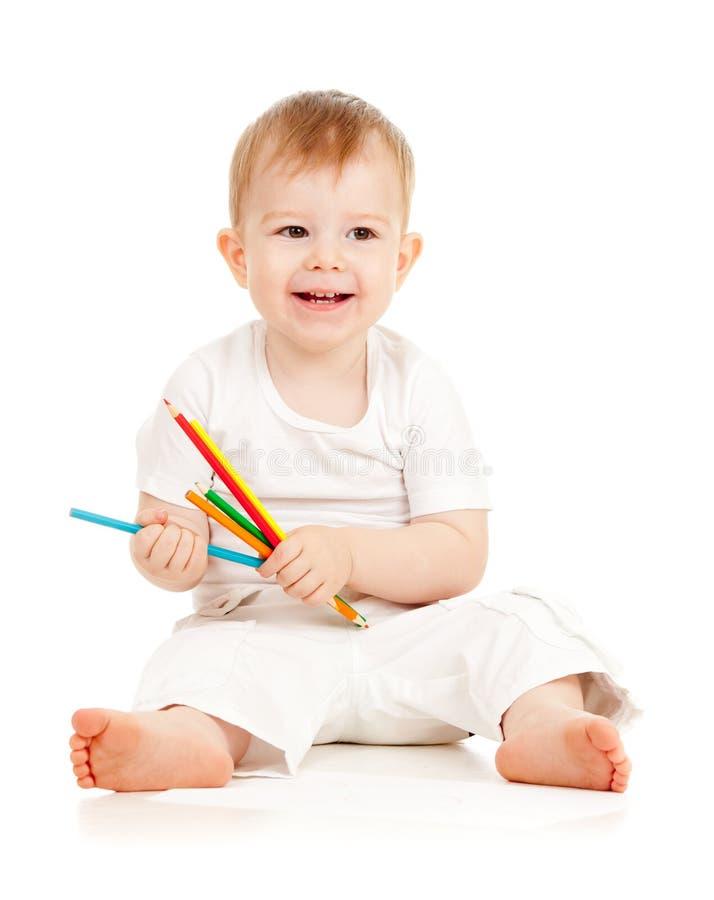 De grappige zitting van de babyjongen met kleurenpotloden royalty-vrije stock foto's