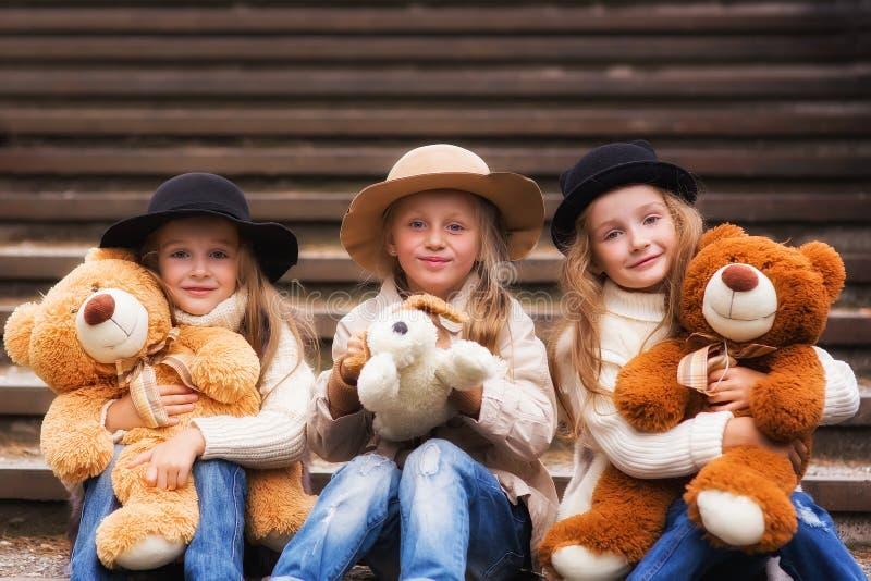 De grappige zitting van het meisjesmeisje op de treden met zacht speelgoed in het park royalty-vrije stock afbeelding