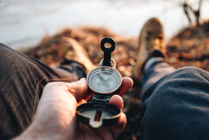 De greep uitstekend kompas van de Hipsterreiziger ter beschikking op achtergrond van hem benen in wandelingslaarzen stock foto