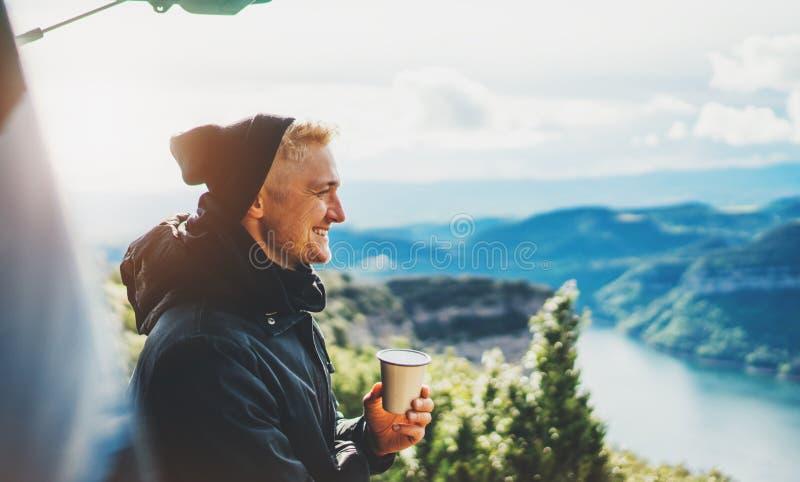 De greep van de Hipstertoerist in handenmok van hete drank, eenzame kerelglimlach geniet van de berg van de zongloed in de auto,  stock foto