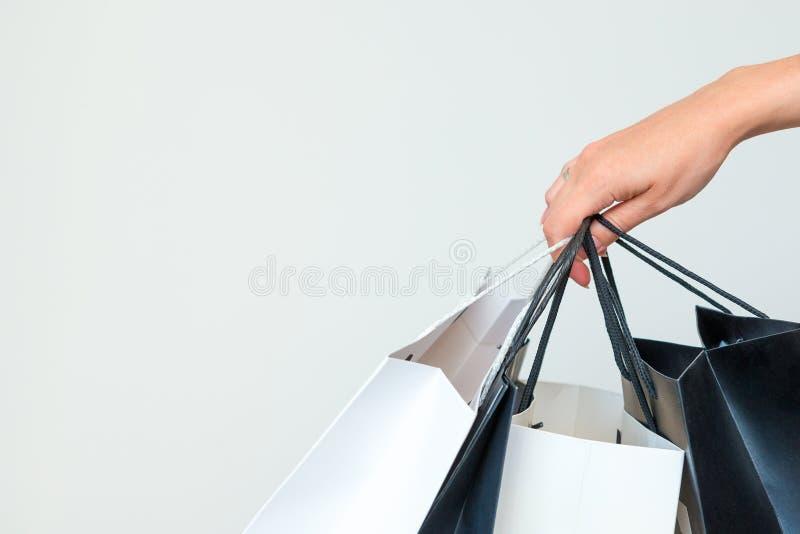 De greep van de vrouwen` s hand zwart-witte het winkelen zakken op lichtgrijze bedelaars stock foto