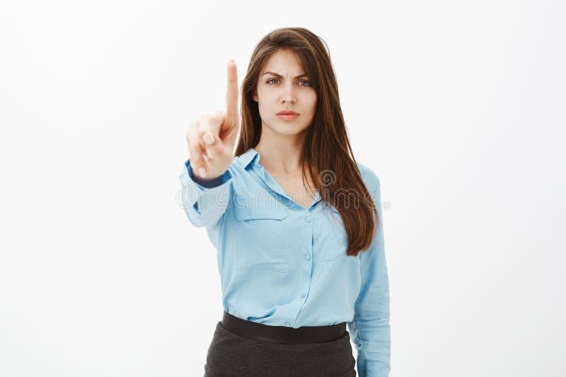 De greep, wacht een seconde Bazige ontstemde aantrekkelijke ondernemer in blauwe officiële blouse die, die en wijsvinger fronsen  royalty-vrije stock foto