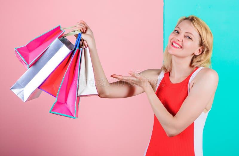 De greepbos van de vrouwen rode kleding het winkelen zakken blauwe roze achtergrond Het meisje geniet van het winkelen of enkel g stock fotografie