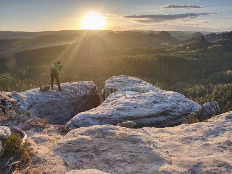 De greepdriepoot van de aardfotograaf met camera mens bij zonsopgang stock fotografie