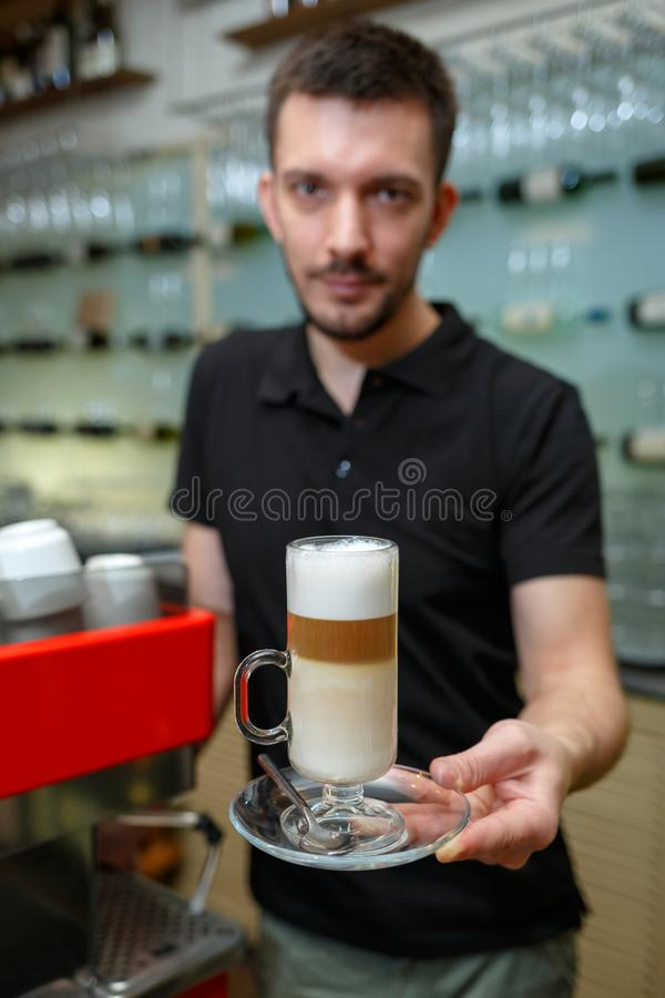 De greepglas die van mensenbarista van latte een cliënt dienen Nadruk op drank Ondiepe Diepte van Gebied royalty-vrije stock foto