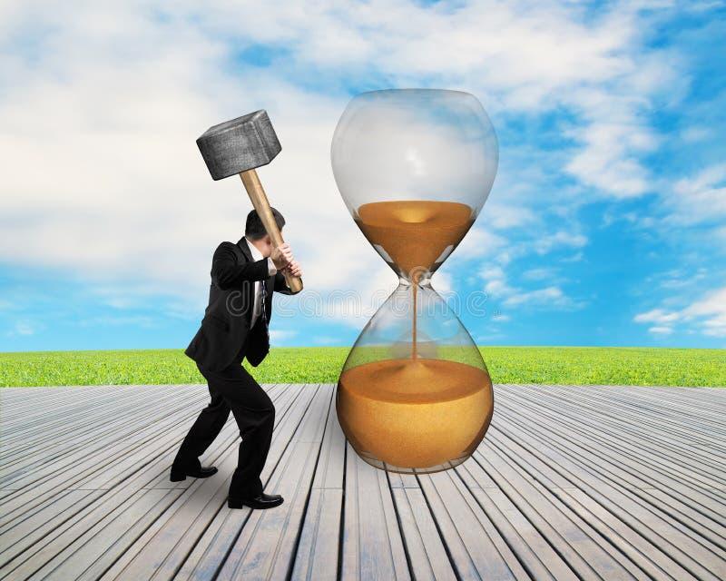 De greephamer van de zakenmanhand om uurglas te raken royalty-vrije stock afbeelding