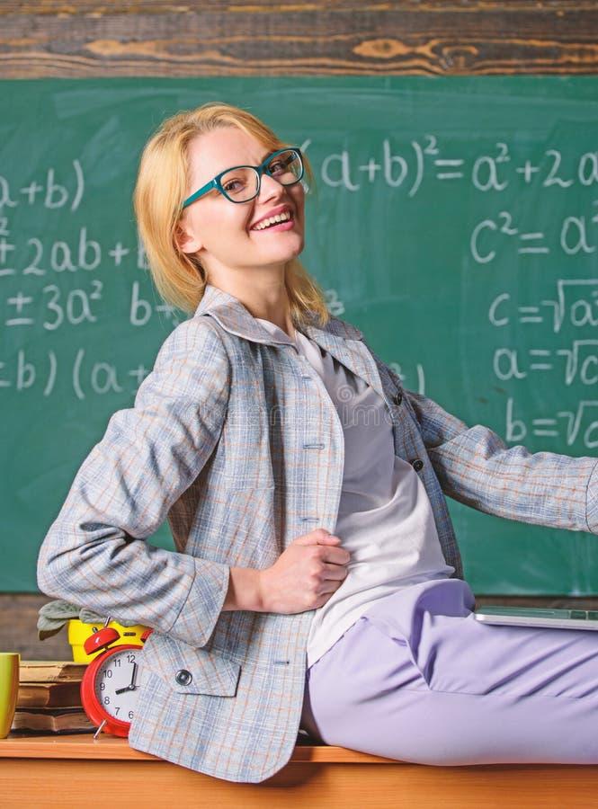 De greeplaptop van de vrouwenleraar zit het bordachtergrond van het lijstklaslokaal Leraar van moderne generatie Niet formele inv stock foto's