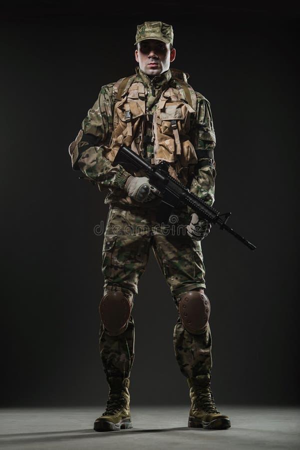 De greepmachinegeweer van de militairmens op een donkere achtergrond royalty-vrije stock afbeelding